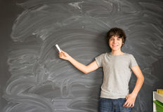 Boy writting on black board. Boy pointing with chalk on empty black board in background Stock Image