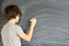 Boy writting on black board Royalty Free Stock Photo
