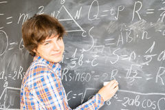 Boy writting on black board Royalty Free Stock Images