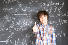Boy writting on black board Royalty Free Stock Photos