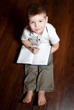 Boy wrote. Little boy doing homework on the wooden floor Royalty Free Stock Photos
