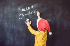 The boy wrote an inscription Merry Cristmas. Christmas tree. Xma Stock Photo