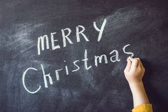 The boy wrote an inscription Merry Cristmas. Christmas tree. Xma Royalty Free Stock Photography