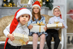 Boy with x-mas gift box and smiling children Royalty Free Stock Photos