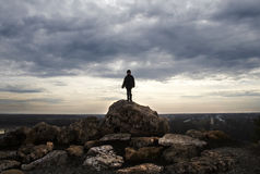 Boy's shape on top of big stone with beautiful landscape in back Stock Photography
