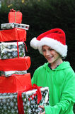 Boy with xmas presents. Boy in santa hat receiving presents Stock Photography