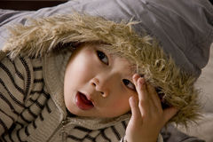 Boy yawning. Picture of a little chinese boy yawning while playing in bed Royalty Free Stock Images