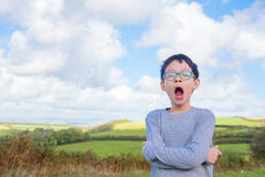 Boy yawning at field in morning Stock Image