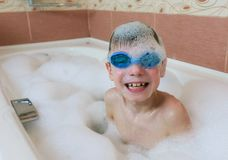 Boy 6-7 years in the foam and goggles for swimming sitting in the bathroom and smiling. royalty free stock photo
