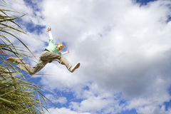Boy (7-9 years) jumping from grass outdoors, low angle view Royalty Free Stock Photo