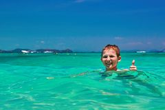 Boy 10 years old bathing in turquoise water tropical sea. Child smiling while showing thumb up. stock image