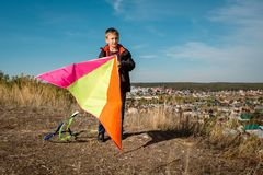 A boy of 10 years old is holding a kite. Bright sunny day. In the background is a small town stock images