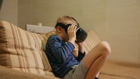 Boy 6-7 years playing at home with the help of virtual reality goggles video games. Close-up stock footage