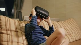 Boy 6-7 years playing at home with the help of virtual reality goggles video games. Close-up stock video