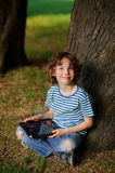 The boy of 8-9 years sits leaning against a tree and holds the tablet in hand. The laddie with a blond curly hair looks in a camera. Jeans are torn on a lap Stock Photos
