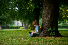 The boy of 8-9 years sits under a big tree, having inclined over the tablet. Royalty Free Stock Photos
