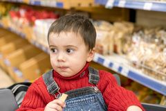 Boy 2 years in a store on the background of bread stock image