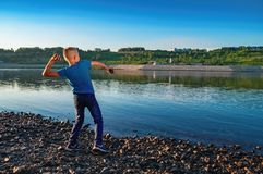 Boy 11-12 years throws stones at the river on the background summer sunset. Child in blue t-shirt and jeans. Back view. stock photography