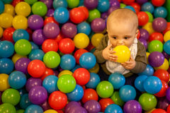 Boy with yellow ball. Little boy having fun in an indoor playground in an activity centre stock photography