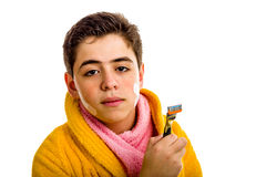 Boy in yellow bathrobe and pink towel holds the razor used for s Royalty Free Stock Photo