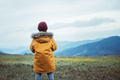 Boy in yellow coat looks on evening autumn mountain valley panorame royalty free stock photos