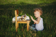 Boy with yellow duckling and rabbit in summer village Royalty Free Stock Image