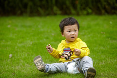 Boy in yellow on grass Stock Photos