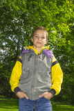 Boy in a yellow hoodie against green trees background Stock Images
