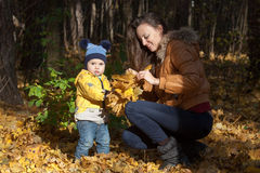 Boy in a yellow jacket collects with mother Royalty Free Stock Photos