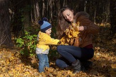 Boy in a yellow jacket helps mother Stock Photography