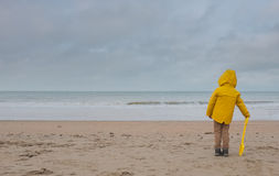 A Boy in a Yellow Raincoat on a Deserted Beach on a Cloudy Day Royalty Free Stock Photos