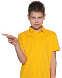 Boy in yellow shirt shows her forefinger to the side Royalty Free Stock Photography