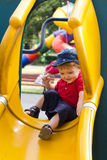 Boy in yellow slide Stock Photos
