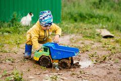 The boy in yellow suit playing with a toy car in the dirt. The boy in the street playing with a toy car stock image