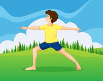 A boy with a yellow t-shirt doing yoga near the pine trees Stock Photography