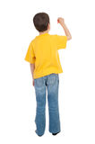Boy in yellow t-shirt writes Stock Photos