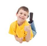Boy in yellow tshirt lying Royalty Free Stock Photos