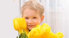 Boy with yellow tulips Stock Photos