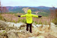 Boy in yellow warm jacket stand on a rock in a cold windy spring day. Active lifestyle, outdoor activities, hike Royalty Free Stock Images