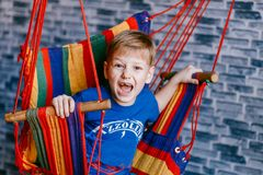 The boy yells with his mouth open. And swinging in the hammock Stock Photos