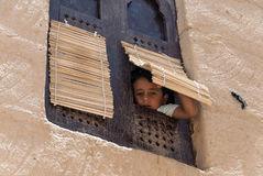 Boy in Yemen. An unidentified boy looks at the camera through his window on May 8, 2007 in Al Hajarayn, Yemen. Although infant mortality is high, children in Stock Photography