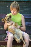 Boy with a young lion. In hands Royalty Free Stock Photography