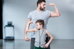Boy with young man, his trainer or father showing muscles Stock Images