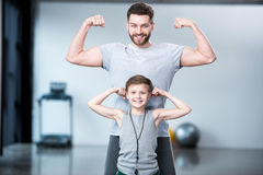 Boy with young man, his trainer or father showing muscles Royalty Free Stock Images