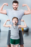 Boy with young man, his trainer or father showing muscles Stock Image
