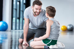 Boy with young man, his trainer or father sitting on floor Royalty Free Stock Photos