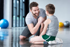 Boy with young man, his trainer or father sitting on floor Royalty Free Stock Photo