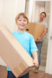 Boy with young man on moving day. Carrying cardboard box Royalty Free Stock Photos