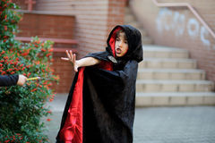 Boy of younger school age in a black-red cloak portrays the evil sorcerer. Boy has a mysterious look. He does the relevant movements by hands Stock Photo
