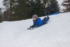 Boy zooms down the hill. Royalty Free Stock Images